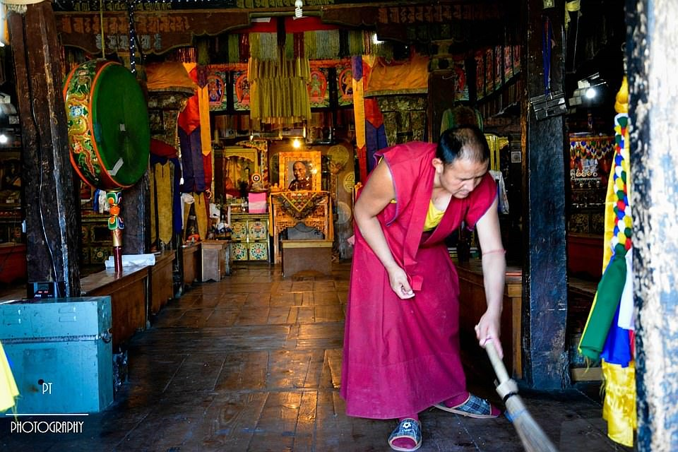 A monk sweeping the sacred prayer hall
