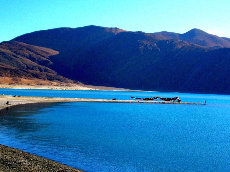 Crystal clear water and fluttering prayer flags at Pangong Tso